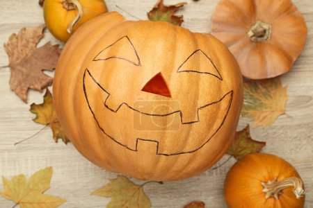 Halloween pumpkin with dry leaves on wooden table