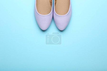 Purple female shoes on blue background