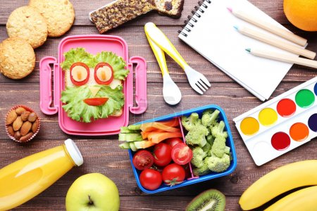 School lunch box with vegetables and fruits on brown wooden table