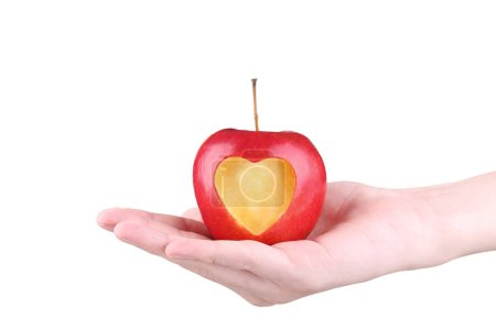 Female hands holding red apple with cutout heart shape on white background