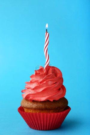 Délicieux petit gâteau avec une bougie sur fond bleu