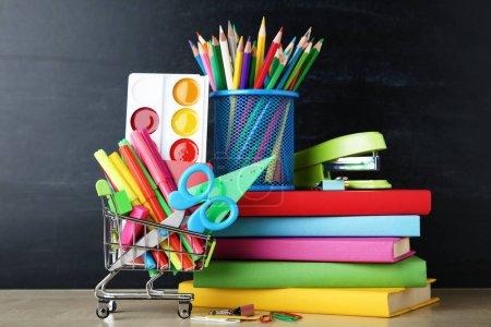 School supplies with books on blackboard background