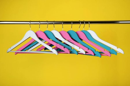 Colorful clothes hangers on yellow background