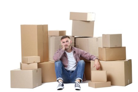 Photo for Young man with cardboard boxes sitting on floor on white background - Royalty Free Image