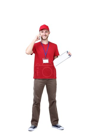 Delivery man with clipboard talking on smartphone isolated on white background