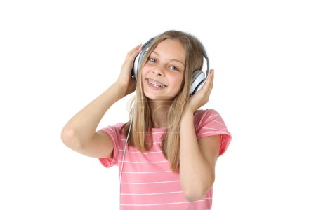smiling girl listening to music on headphones and looking at camera isolated on white background