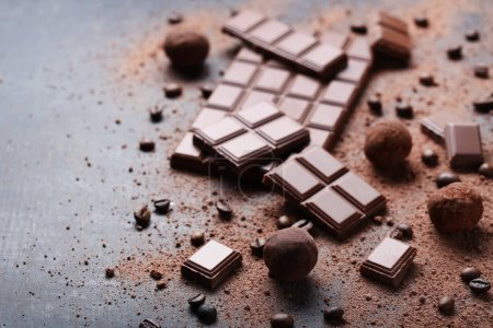 Chocolate pieces with coffee beans and cocoa powder on wooden table