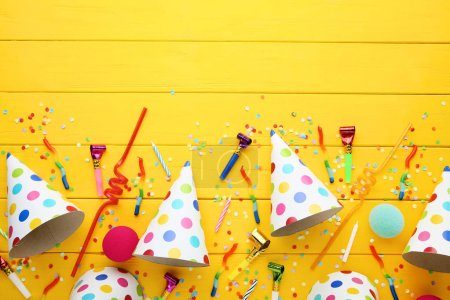 Birthday paper caps with candles and blowers on yellow wooden table