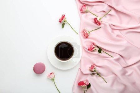 Photo pour Fleurs roses avec une tasse de café et tissu de satin sur fond blanc - image libre de droit
