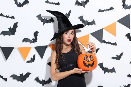Photo pour Jeune femme en costume d'Halloween avec seau de citrouille sur fond blanc - image libre de droit