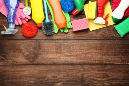 Bouteilles avec détergent et outils de nettoyage sur fond bois