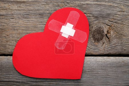 Photo for Red paper heart with adhesive bandage on wooden background - Royalty Free Image