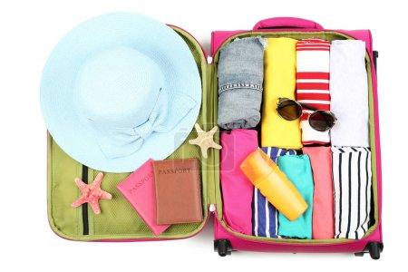 Photo pour Valise ouverte avec vêtements, lunettes de soleil, passeports et bouteille de crème solaire sur fond blanc - image libre de droit