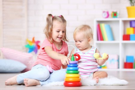 Photo for Little sisters playing with toys at home - Royalty Free Image