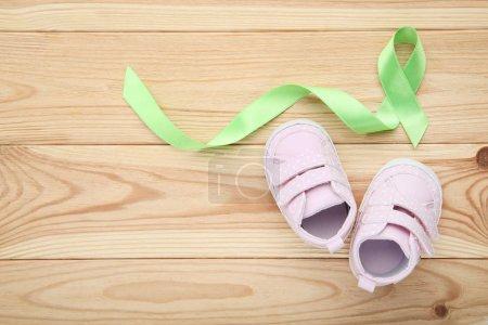 Photo pour Vert de ruban avec des chaussures de bébé sur fond en bois - image libre de droit