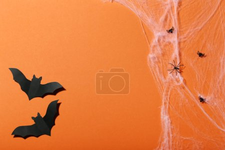 Halloween paper bats with spiders in cobweb on orange background