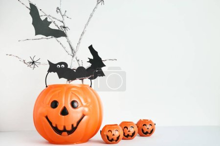 Halloween buckets with paper bats and spiders on grey background