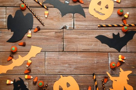 Halloween candies with paper decorations on brown wooden table