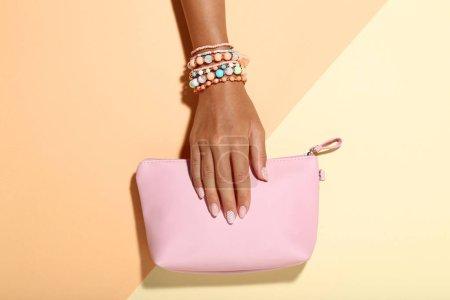 Photo pour Main féminine avec bracelets et sac à main sur fond coloré - image libre de droit