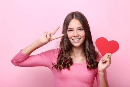 Photo pour Jeune fille tenant coeur de papier rouge sur fond rose - image libre de droit