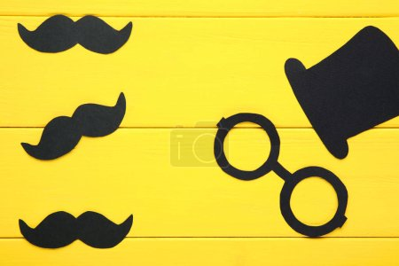 Paper booth props for party on yellow wooden background