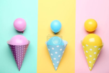 Rubber balloons with birthday paper caps on colorful background