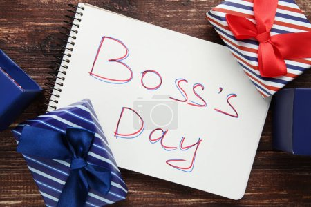 Photo for Inscription Boss Day in notebook with gift boxes on wood - Royalty Free Image