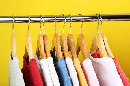 Wooden hangers with clothes on rack on yellow background