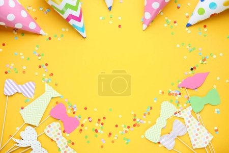 Colorful booth props for party with paper caps on yellow background