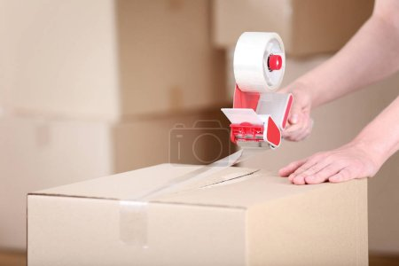 Photo for Female hands packaging cardboard box with dispenser - Royalty Free Image