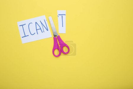 Paper with text I can't and scissors on yellow background