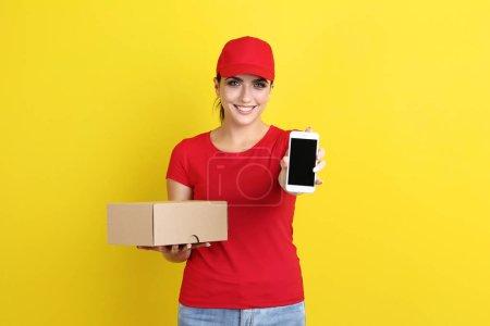 Photo pour Livraison femme avec boîte en carton et smartphone sur fond jaune - image libre de droit