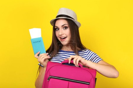 Photo for Young girl with suitcase and passport on yellow background - Royalty Free Image
