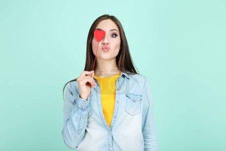 Belle femme tenant coeur rouge sur fond de menthe
