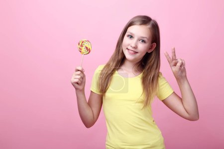 Photo for Cute young girl with lollipop on pink background - Royalty Free Image