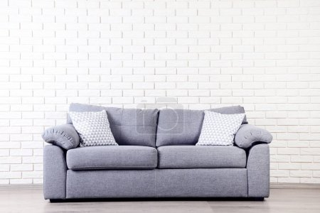 Photo for Modern grey sofa with pillows on brick wall background - Royalty Free Image