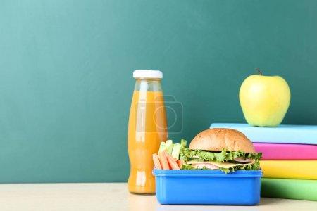 Schulessenbox mit Sandwich und einer Flasche Saft auf der Tafel