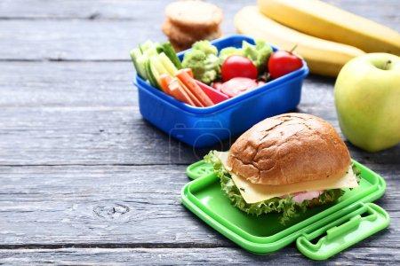 Schulessenbox mit Sandwich und Gemüse auf Holztisch