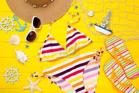 Traje de baño de moda con ropa y conchas de mar en madera amarilla ta