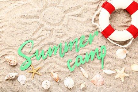 Texto en papel Campamento de verano con conchas marinas y boya salvavidas en arena de playa