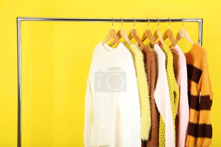 Photo for Fashion sweaters hanging on wooden hanger - Royalty Free Image