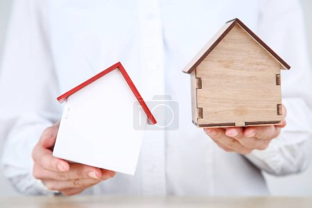 Photo for Female hands holding wooden house models - Royalty Free Image