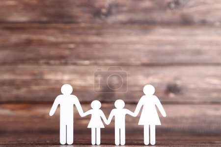 Photo for Family figures on brown wooden background - Royalty Free Image