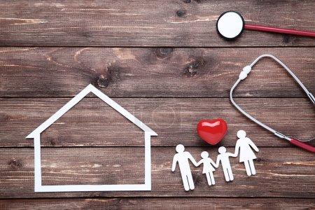 Photo pour Figures de famille avec coeur rouge, maison en papier et stéthoscope sur fond de bois brun - image libre de droit