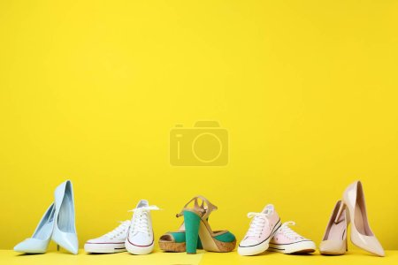 Photo for Different female shoes on yellow background - Royalty Free Image