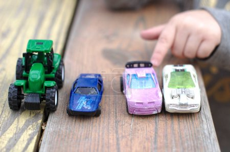 A small children's hand points to one toy car amon...
