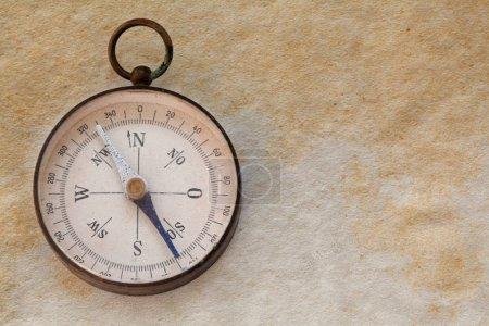 Ancient magnetic exploration compass, navigator. Manuscript aged paper background. copy space. closeup