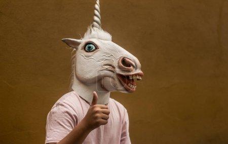 Photo pour Jeune homme en caoutchouc drôle masque licorne - image libre de droit
