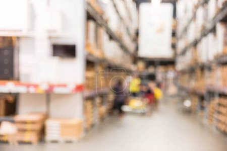 Photo for Blurred customers shopping in large furniture warehouse with row of aisles and bins from floor to ceiling. Defocused background industrial storehouse interior. Inventory, wholesale, logistic, export - Royalty Free Image