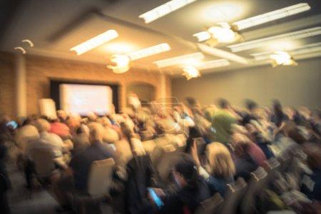 Photo pour Réunion de séminaire d'affaires floue avec écran de projecteur LED et discours de haut-parleur sur scène. Audience arrière déconcentrée dans la salle de conférence, écoute talk-show aux États-Unis. Éducation, concept d'entreprise - image libre de droit